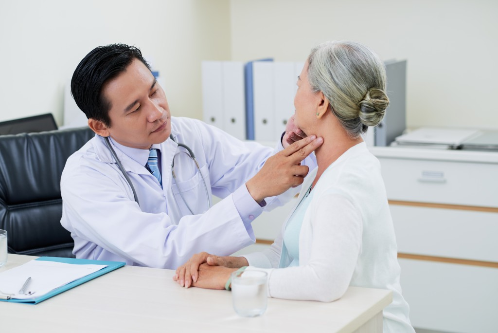 doctor checking neck of woman