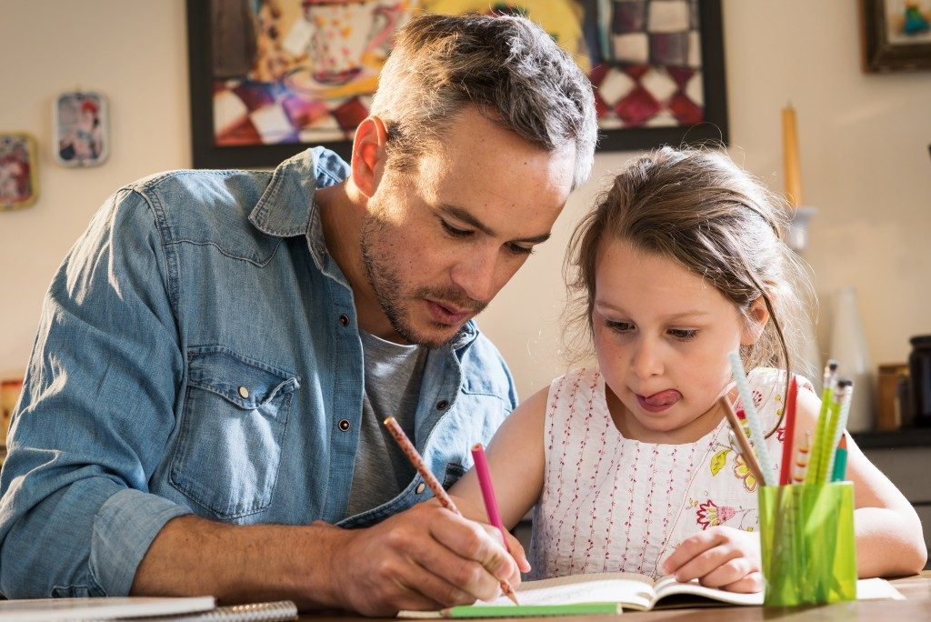 A father helps his little daughter to do her homework for the schoo