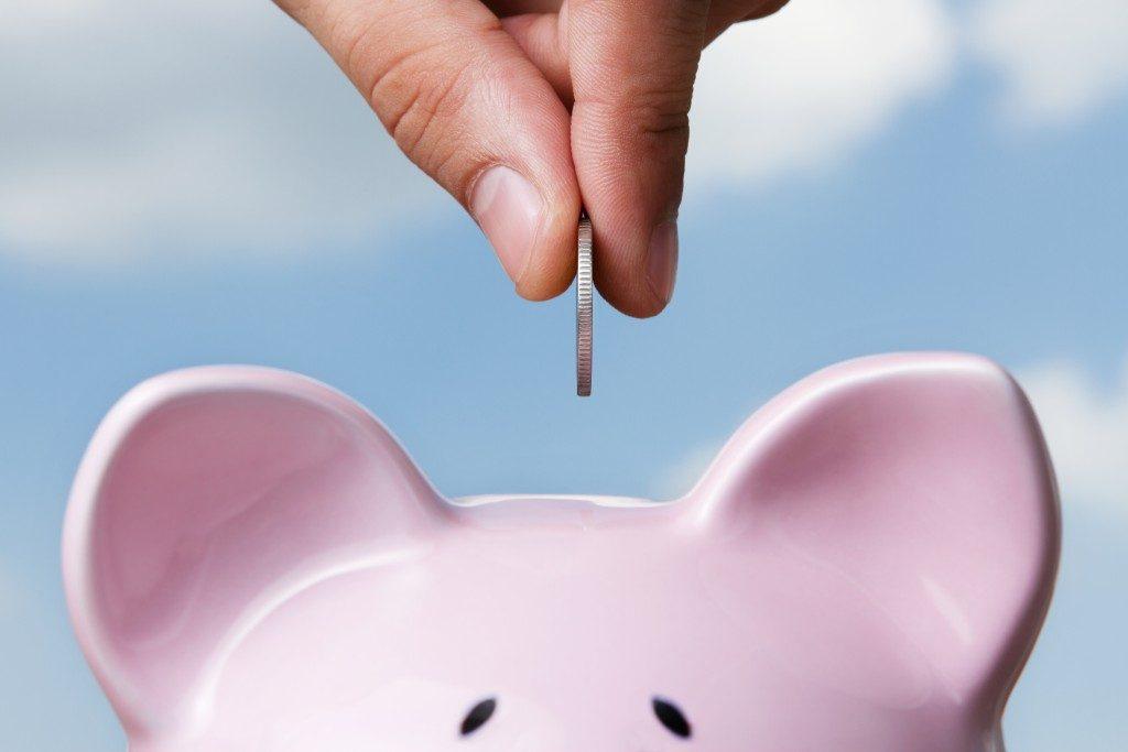 Placing coin inside piggy bank