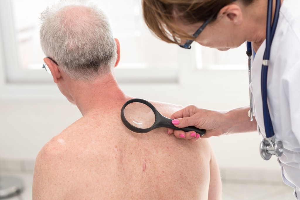 doctor examining back of old man