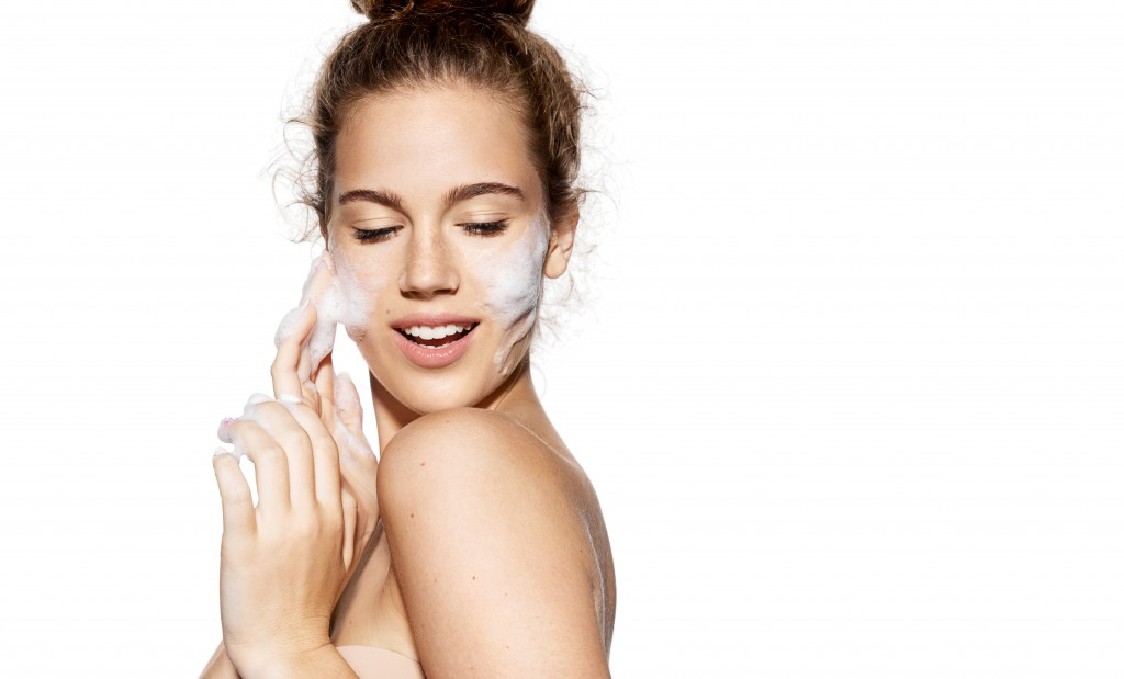 woman applying a skin care product on her cheeks