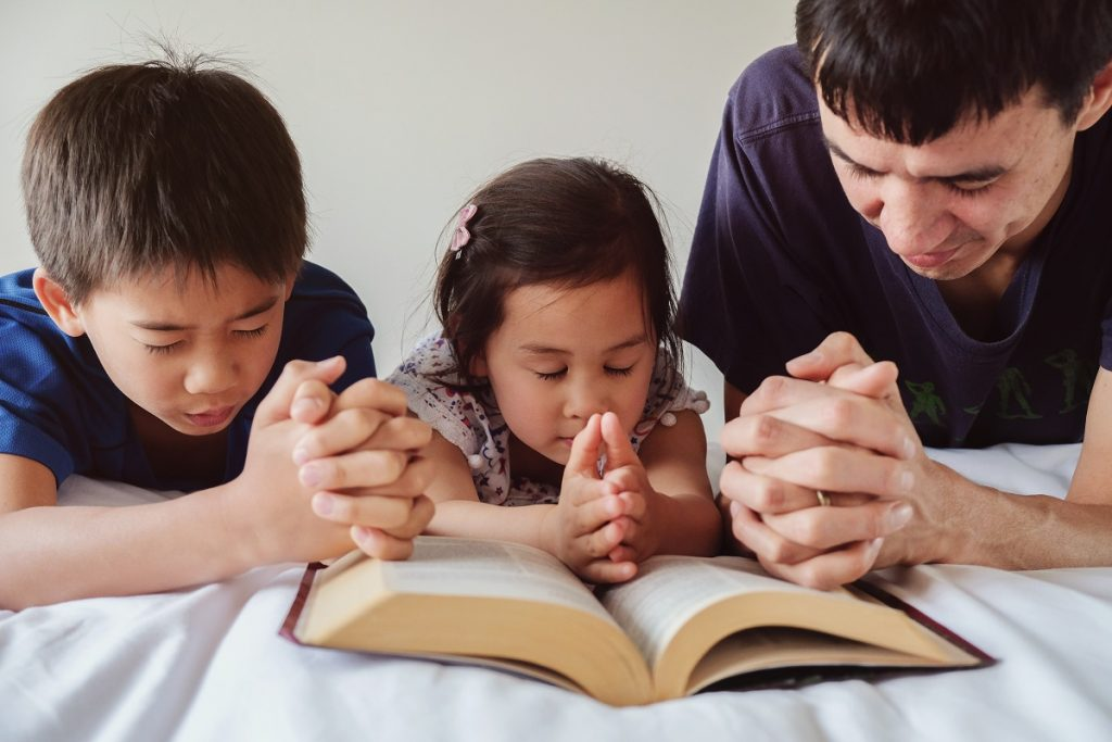 Family praying with a bible