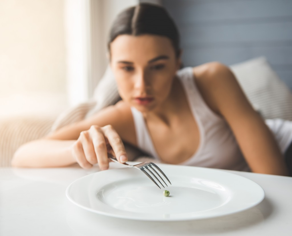 a woman with an eating disorder playing the pea on the plate