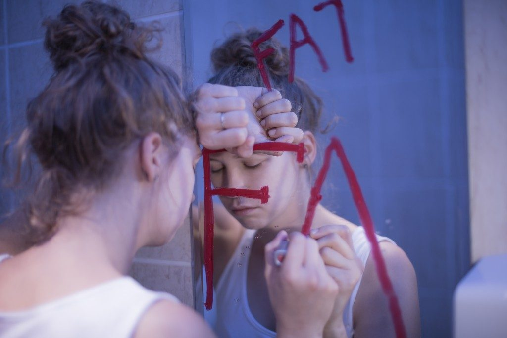 woman facing the mirror having a mental illness