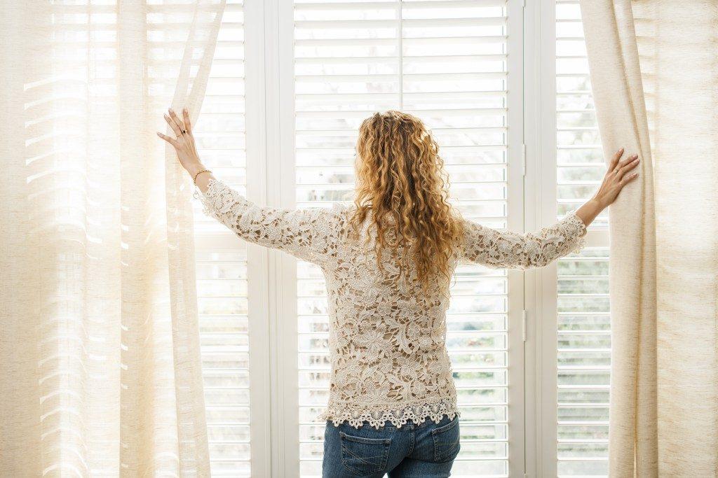 woman parting the sheer drapes