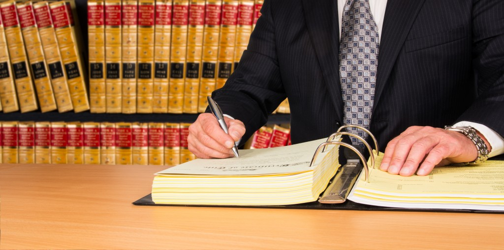 half dhot of a paralegal writing in a document