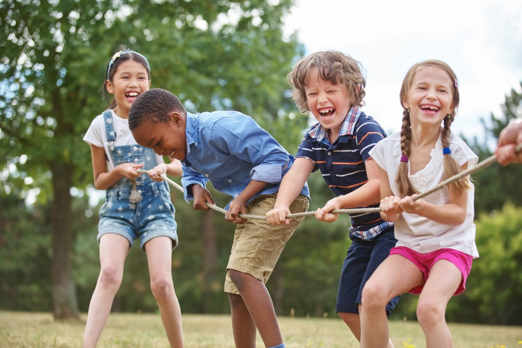 children playing tug o war at the park