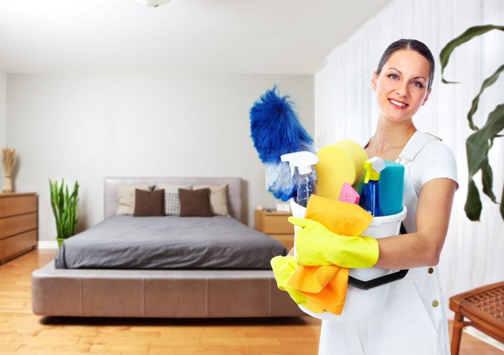 Woman cleaning the bedroom