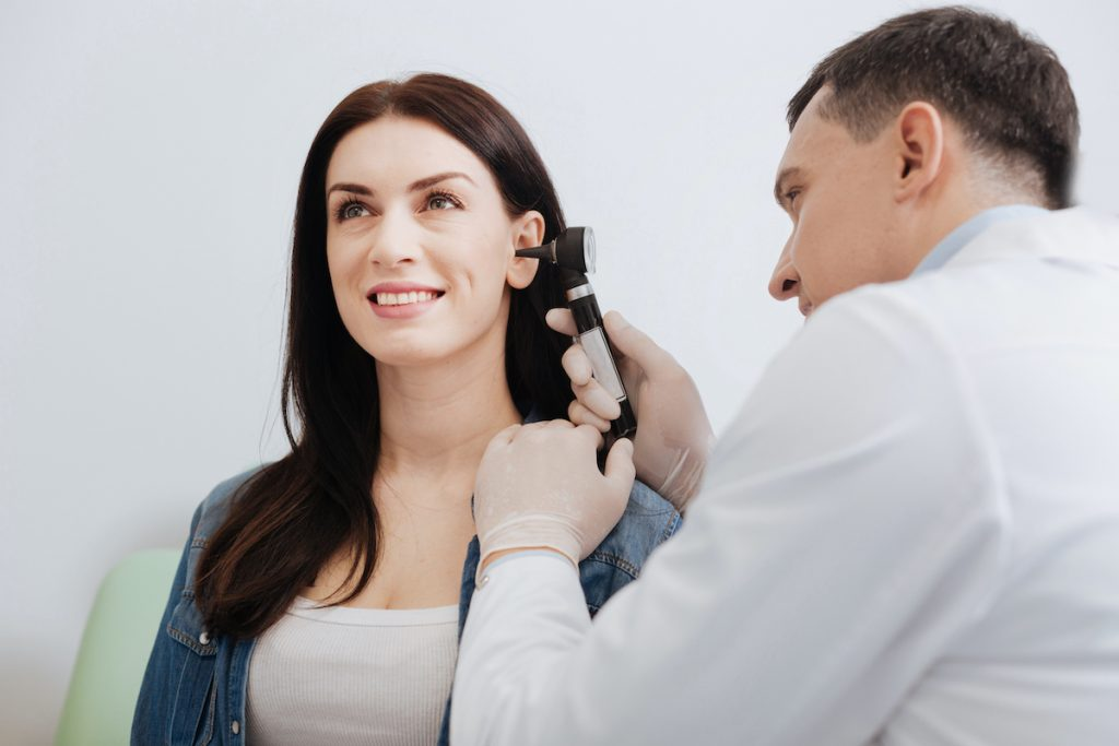 doctor checking woman's ears
