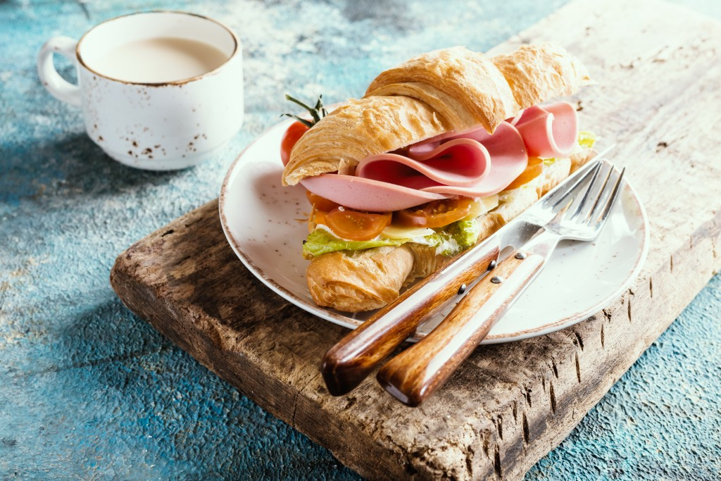 croissant sandwich with ham, cheese and salad leaf with coffee on blue table