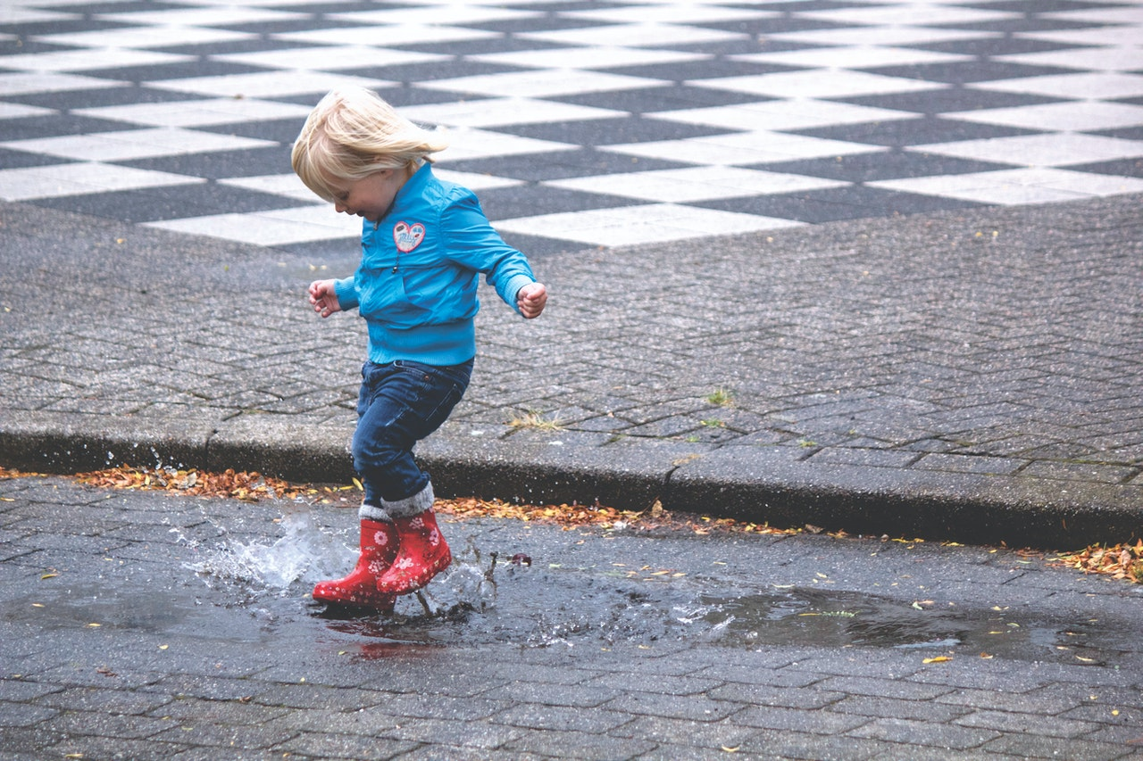 child playing in the rain puddle