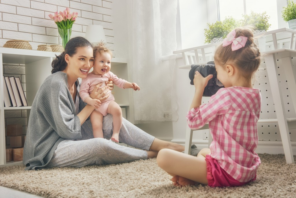 toddler taking a picture of mother and baby