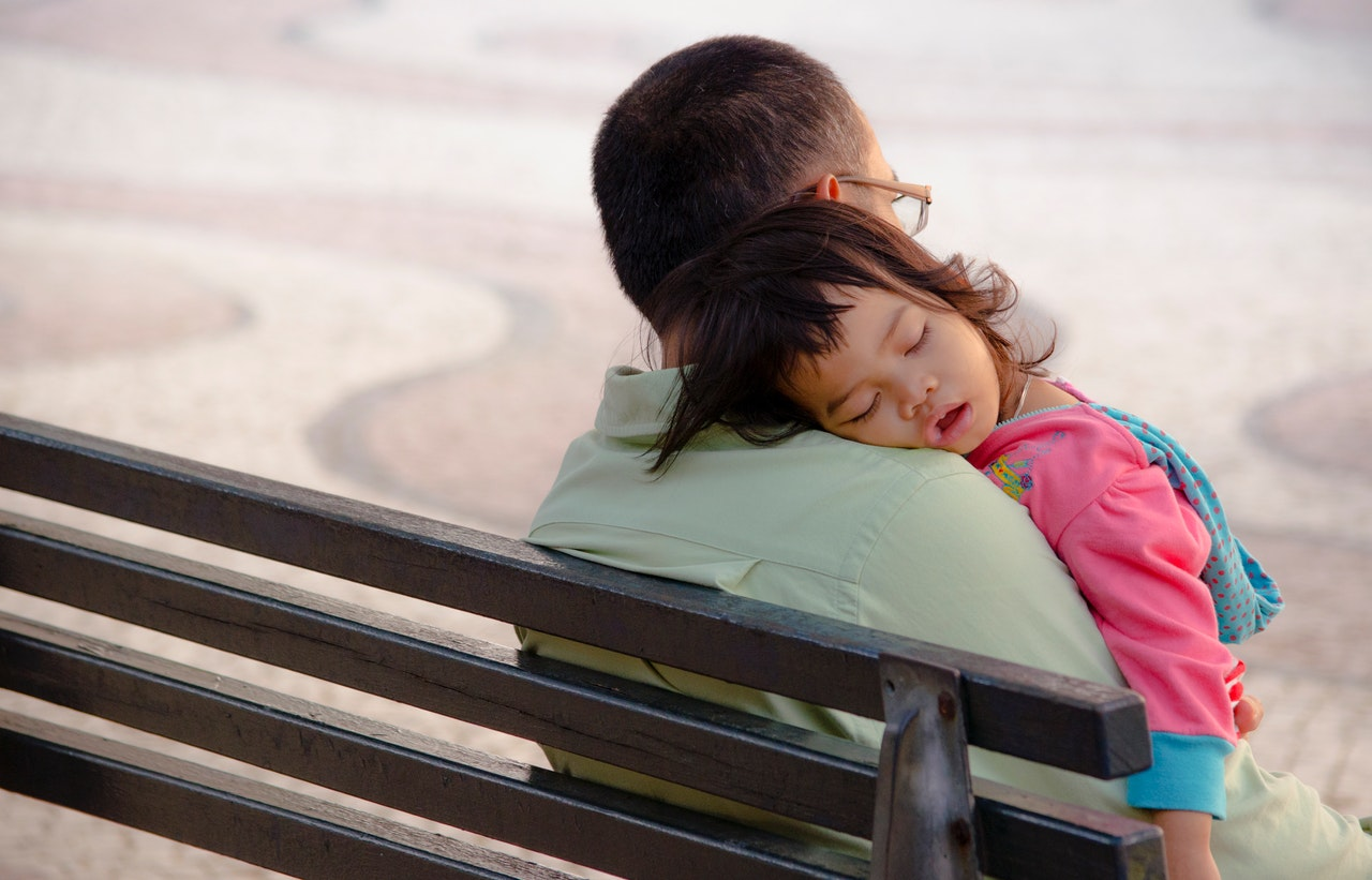 young girl sleeping on father's shoulder