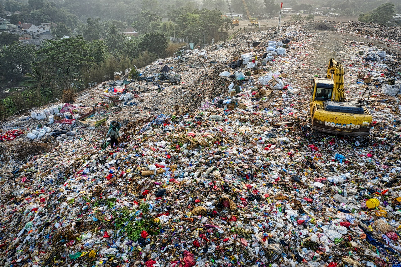 an excavator in a mountain of garbage