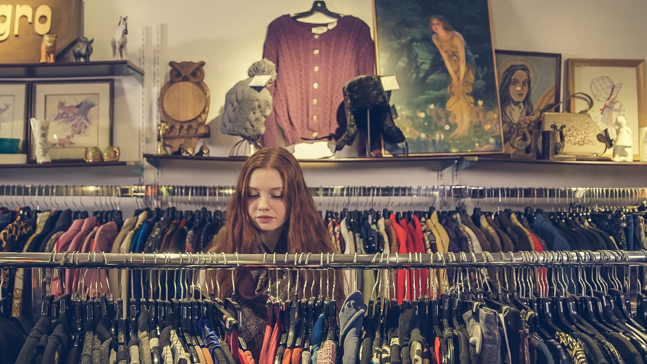 woman looking at clothing in thrift store