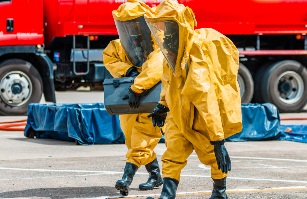 two person transporting hazardous chemical waste