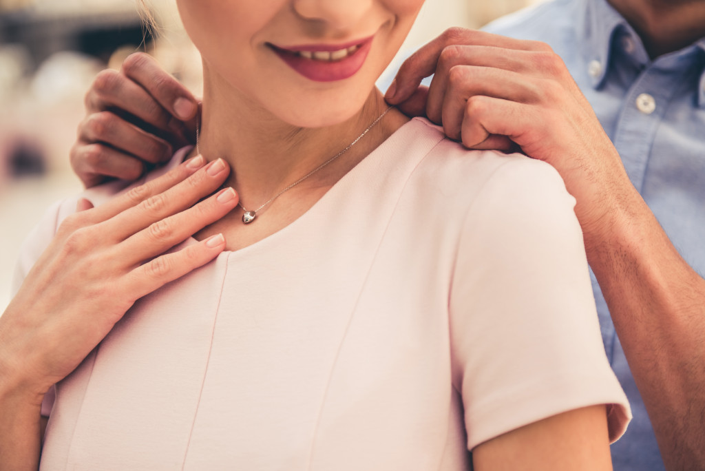 man giving his partner a necklace