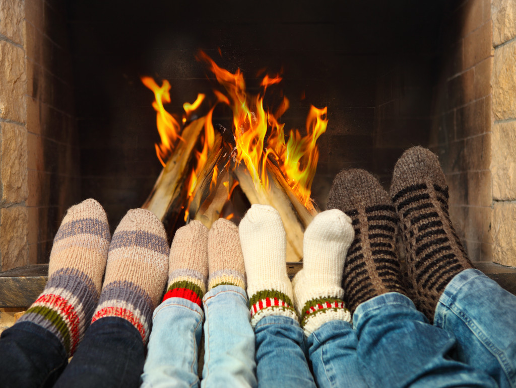 four pairs of feet in front of a fireplace